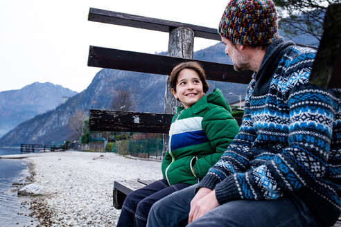 Boy and father sitting chatting on lakeside pier, Lake Como, Onno, Lombardy, Italy - CUF49231