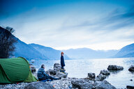 Father and son camping by lakeside, Onno, Lombardy, Italy - CUF49234
