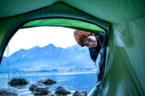 Boy peering into tent by lakeside, Onno, Lombardy, Italy - CUF49237