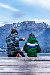 Boy and father sitting pointing on lakeside pier, rear view, Lake Como, Onno, Lombardy, Italy - CUF49252