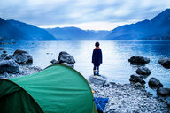 Boy looking out over lake, rear view, Lake Como, Onno, Lombardy, Italy - CUF49255