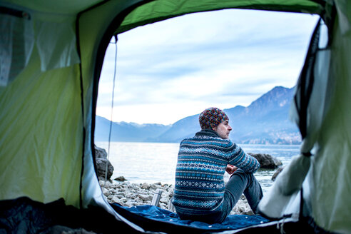 Man camping on lakeside, view from inside tent, Onno, Lombardy, Italy - CUF49258
