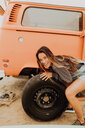 Young woman changing recreational vehicle tyre at beach, portrait, Jalama, California, USA - ISF20543