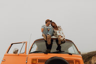 Young couple sitting on top of recreational vehicle, Jalama, California, USA - ISF20558