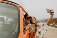 Young couple on roadside in recreational vehicle taking smartphone selfie,  portrait, Jalama, California, USA - ISF20561