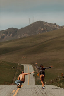 Young skateboarder couple skateboarding down rural road, rear view, Jalama, California, USA - ISF20573