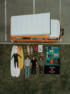 Three young surfers with surfing equipment and recreational vehicle lying on backs by beach carpark, overhead portrait, Ventura, California, USA - ISF20591