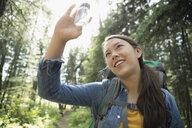 Curious teenage girl outdoor school student examining specimen in jar, hiking in woods - HEROF20677