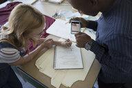 Fashion designers sketching and using camera phone at workbench in studio - HEROF20743