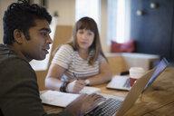 Designers working at laptops, planning in office meeting - HEROF20785