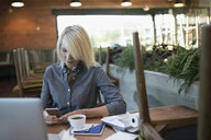 Female cafe business owner texting with cell phone at laptop - HEROF20821