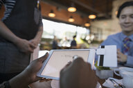 Female customer paying, signing digital tablet credit card swiper at restaurant table - HEROF20827