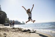 Exuberant girl jumping on sunny ocean beach - HEROF20842