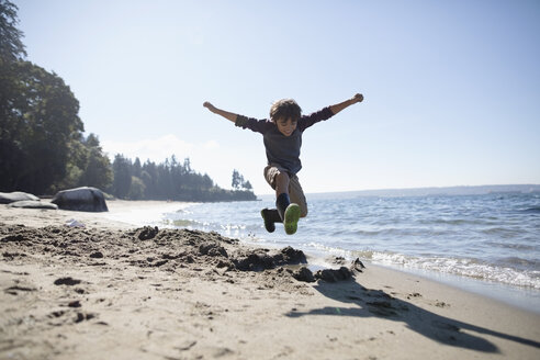 Exuberant boy jumping on sunny ocean beach - HEROF20845