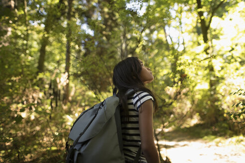 Curious girl with backpack exploring in woods, looking up at trees in wonder - HEROF20848