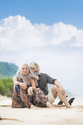Portrait of happy senior hippie couple sitting side by side on the beach - SBOF01703