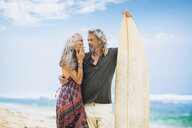 Senior hippie couple with surfboard on the beach - SBOF01706