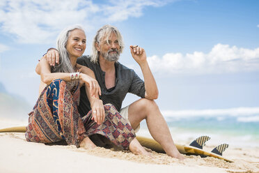 Portrait of senior hippie couple with surfboard relaxing on the beach - SBOF01709