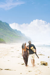 Back view of senior hippie couple with guitar strolling side by side on the beach - SBOF01712