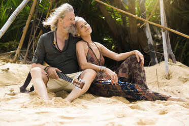 Portrait of happy senior hippie couple with guitar relaxing on the beach - SBOF01715