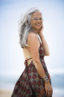 Portrait of smiling senior hippie woman with sandy back on the beach - SBOF01718