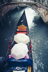Italy, Venice, tourists in a gondola sheltering under umbrellas because of heavy rain - PPXF00168