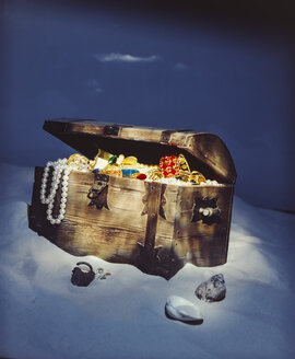 Treasure chest at the shore filled with jewels pearls and gold coins - PPXF00174