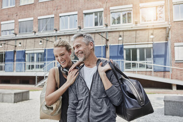 Portrait of mature man and young woman with sports bag in front of gym - RORF01714