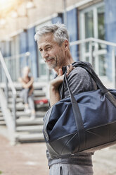 Portrait of mature man with sports bag standing in front of gym - RORF01720