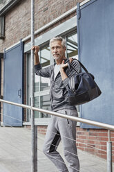 Portrait of mature man with sports bag standing in front of gym - RORF01723