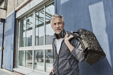 Portrait of mature man with headphones and camouflage sports bag in front of gym - RORF01729