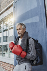 Portrait of mature man with towel, sports bag and red boxing gloves standing in front of gym - RORF01732