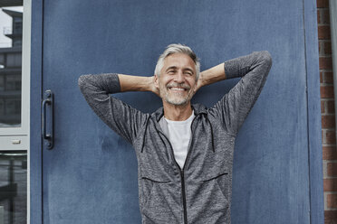 Portrait of laughing mature man in front of gym - RORF01741
