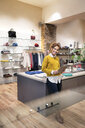 Young woman working in fashion store, using digital tablet - PESF01373