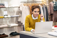 Young woman working in fashion store, using laptop - PESF01376
