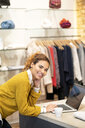 Young woman working in fashion store, using laptop - PESF01379