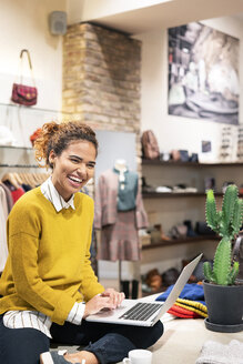 Young woman working in fashion store, using laptop - PESF01382