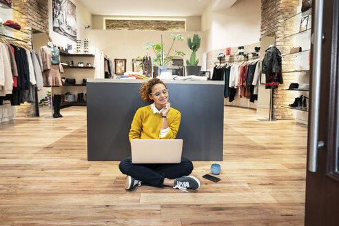 Young woman working in fashion store, using laptop - PESF01388