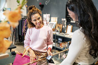 Young customer paying contactless in a fashion store - PESF01409