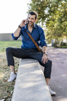 Portrait of smiling man on the phone sitting on a wall outdoors - GIOF05703