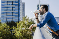 Profile of man leaning on railing drinking coffee to go - GIOF05727