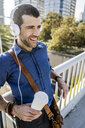 Portrait of smiling man with coffee to go listening music with headphones - GIOF05730