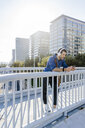 Singing man leaning on railing of footbridge listening music with headphones and smartphone - GIOF05733