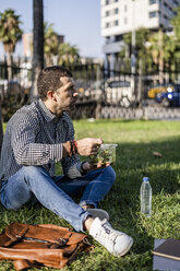 Man sitting on a meadow in city park eating mixed salad - GIOF05745
