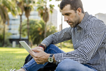 Man sitting on meadow in city park looking at digital tablet - GIOF05760