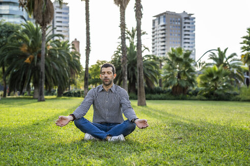 Man sitting on meadow in city park doing yoga exercise - GIOF05763