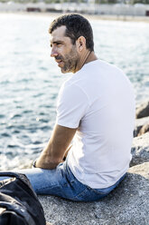 Man sitting on a rock in front of the sea relaxing - GIOF05766