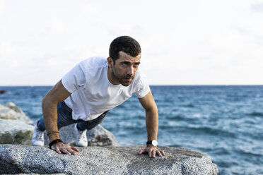 Man doing doing pushups on rock in front of the sea - GIOF05775