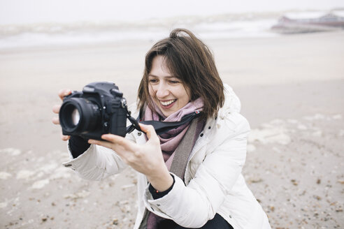 Portrait of relaxed woman taking photos on the beach with camera - KMKF00749