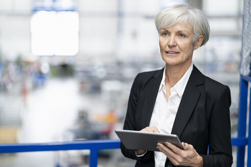 Senior businesswoman using tablet in a factory - DIGF05644